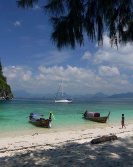 a shady tropical beach with local wooden boats