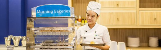 photo of woman in chefs clothing with plate of bakery products