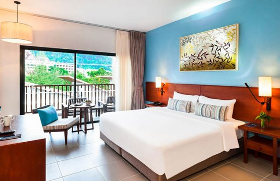 Image of king size bed in hotel room with balcony