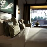 photo of king size bed in resort suite with balcony