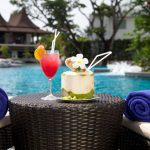 Picture of table with coconut and drinks at resort poolside