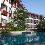 Photo of hotel building with landscaped swimming pool