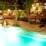 Photo of resort swimming pool lit at night time