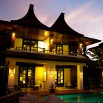 picture of Thai style resort building lit for evening