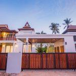 photo of external villa entrance gare and villa roofline. Lit at dusk in Krabi