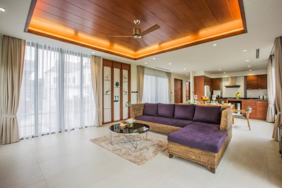 photo of spacious open plan living area with large sofa and view to swimming pool