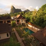 photo of elevated aerial view of small villa resort with tropical mountain background