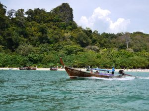 a traditional longtail passing railay beach