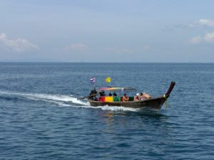 a traditional longtail boat taking customers between islands in krabi
