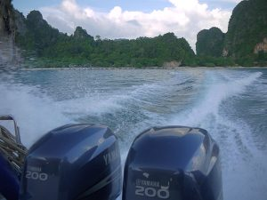 view from the back of a two engine speedboat leaving railay beach krabi
